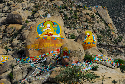 large boulders on a mountainside painted with Buddhist iconography and draped about with Tibetan flag strings